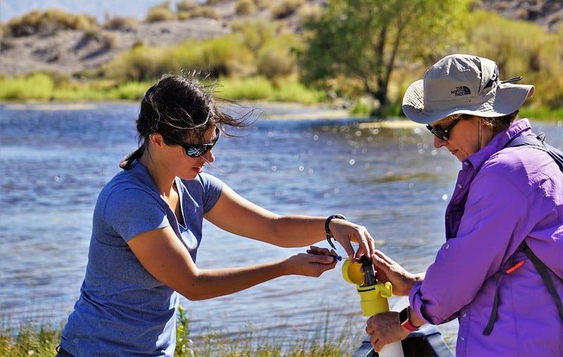 Desert Research Institute scientist Gabrielle Boisrame, Ph.D., (left) and graduate research assistant Rose Shillito from the University of Nevada, Las Vegas (right) prepare a pressure sensor for measuring water depth
