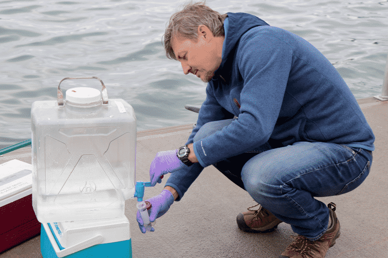 Bigelow Laboratory scientist Ramunas Stepanauskas collects a water sample on the institute's dock.