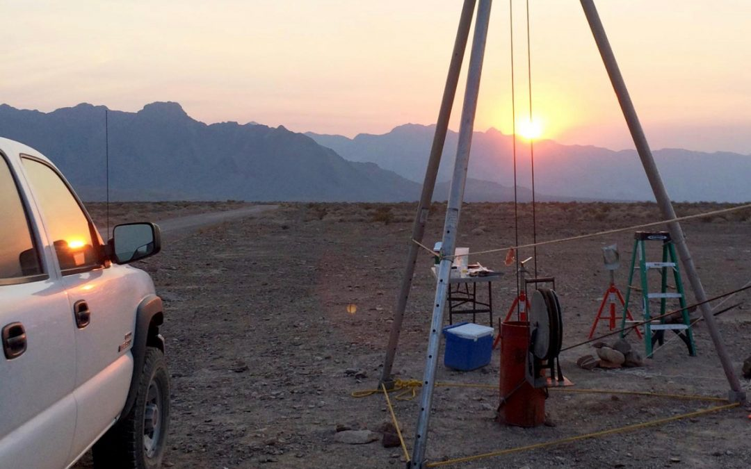 Equipment for subsurface sampling of microbes stands in Death Valley, California. Sun setting in the background.
