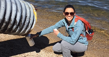 researcher gathering water from a pipe in Lake Tahoe