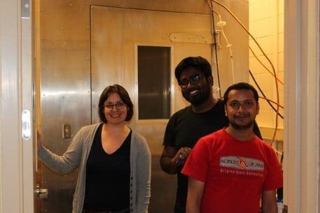The OAL team, Assistant Research Professor V. Samburova; Ph.D. students: Chiranjivi Bhattarai and Deep Sengupta stand near DRI's combustion chamber