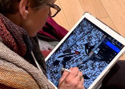 A teacher works on a digital art design.