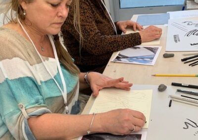 Two teachers sit at a table and sketch scenes from nature.